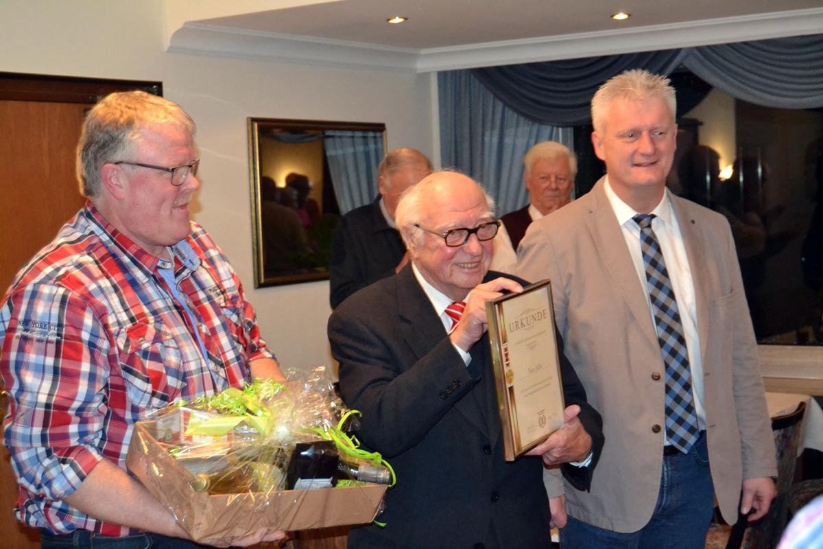 Wolfgang Gödde (links) und Rüdiger Beul (rechts) überreichen Theo Jütte (Mitte) die Ehrenurkunde für 70 Jahre aktives Singen.